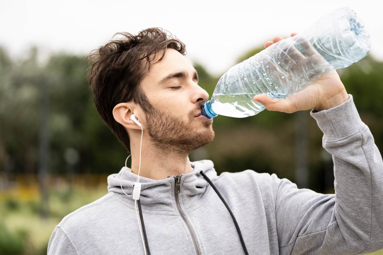 one person;man;adult;male;music;photography;healthy lifestyle;refreshment;plastic;sweatshirt;drinking water;earphones;public park;day;brown hair;beard;drinking;standing;eyes closed;young;listening;holding;headshot;front view;close-up;color image;focus on foreground;horizontal;park;healthy living;close-ups;color images;adults;men;males;plastics;earphone;sweatshirts;public parks;beards;horizontals;refreshments;tight shot;close shot;foreground in focus;eyes shut;one individual;person;earbuds;drinkable water;potable water;daytime;brown haired;colour image;head shot;close shots;tight shots;colour images;eye shut;eye closed;parks;earbud;sweat-shirts;listen;listens;standing up;holds;hold;from the front;daylight;close up;brownhaired;day-time;sweat-shirt;thirsty;water;bottle;drink;grey;lifestyle;technology;casual;hood;outdoors;photoalto,people