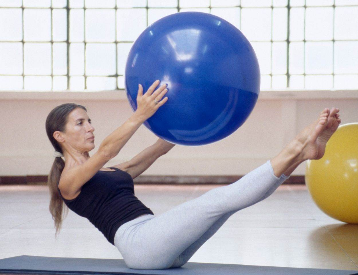 woman;female;exercises;exercise;pilates;exercising;system;method;technique;fitness;fit;healthy;health;balance;balancing;arm;stomach;leg;muscle;muscles;posture;pastime;hobby;sport;sporting;leisure;people;activity;activities;mat;floor;gym;gymnasium;swiss;ball