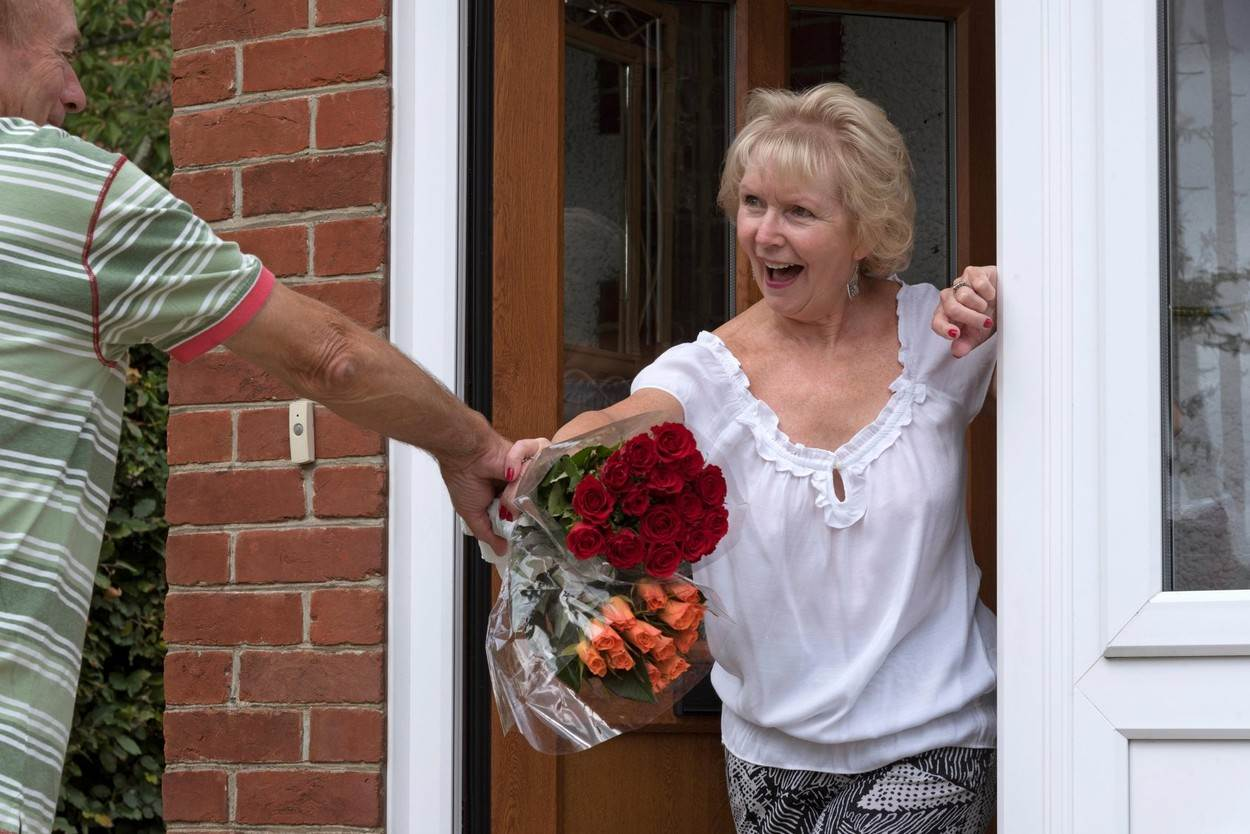 man;woman;flowers;bunch;roses;red;surprise;love;elderly;bunch flowers;husband;couple;couples;bunches;rose;orange;selection;gift;present;pensioner;senior;seniors;romance;presentation;lifestyle;gesture;kind;kindly;celebration;tradition;mature;people;front door;door;doorway;home;house;wife;friends;friendly;give;giving;traditions;POV;NOT_EDITORIAL_ONLY