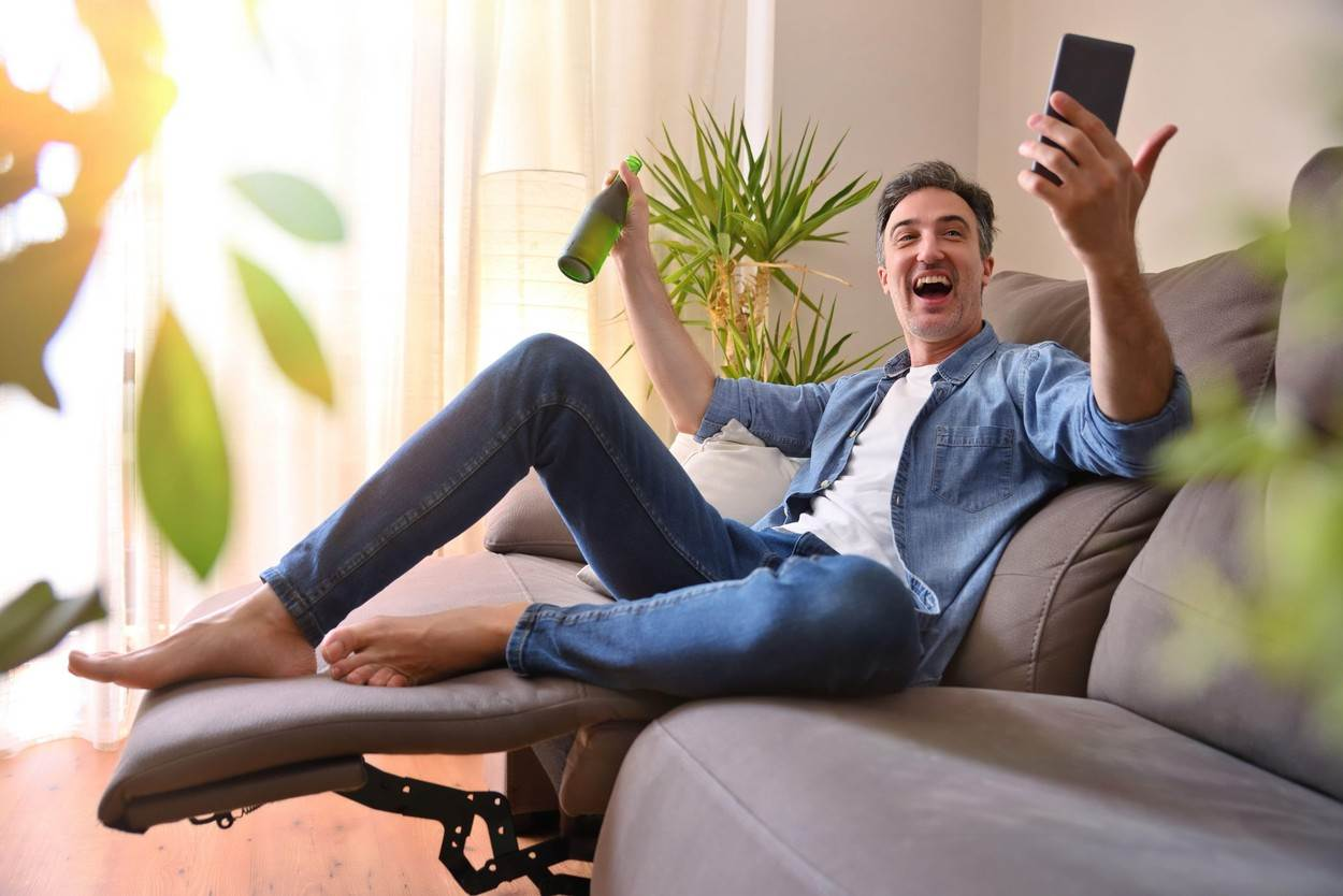 man;leisure;phone;home;beer;video conference;happy;entertainment;friends;virtual;mobile;drinking;fresh;40s;resting;male;fun;cheerful;sofa;warm;summer;sun;lifestyle;one;person;recreational;room;living;videoconference;indoors;interior;rest;adult;people;relax;modern;cold;activity;casual;caucasian;drink;vacation;relaxing;apartment;holiday;stay at home;happiness;NOT_EDITORIAL_ONLY