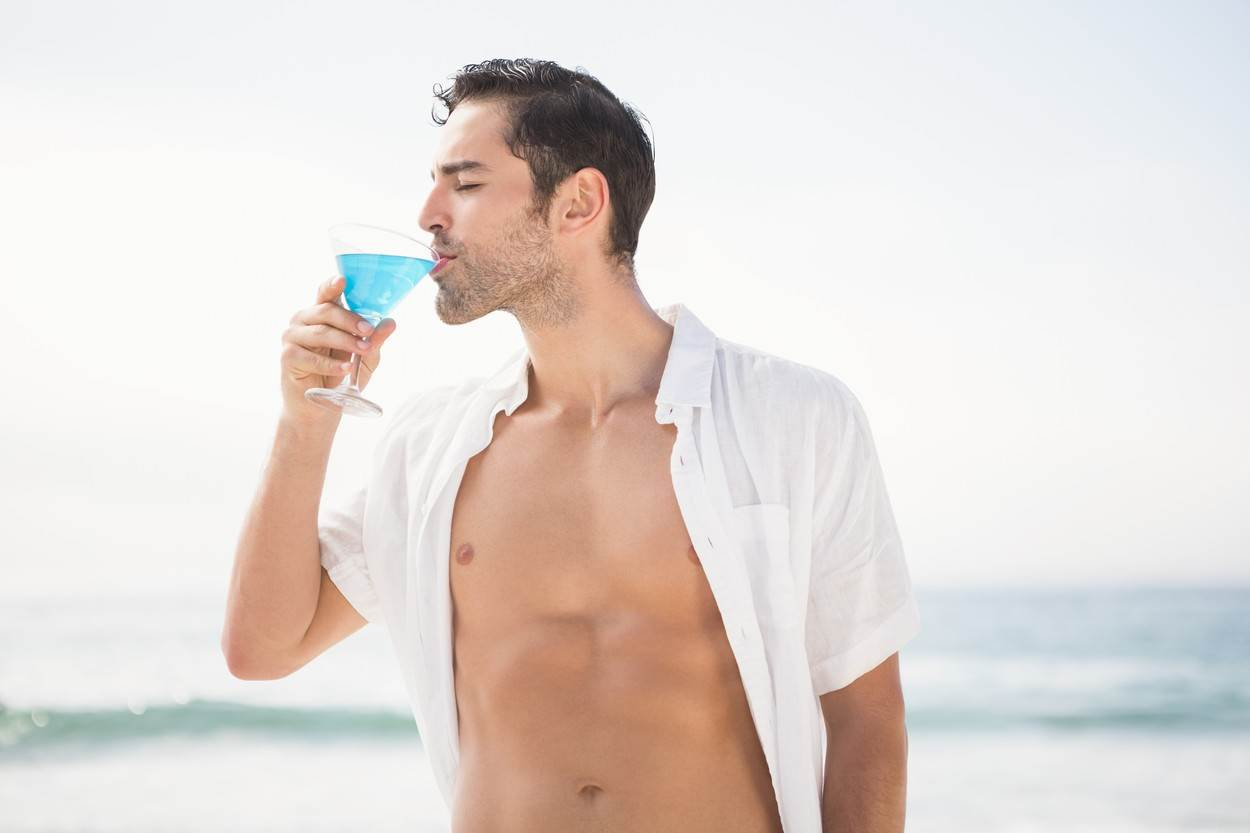 20s;Young Adult;Man;Male;Caucasian;Coastline;Shore;Summertime;Holidays;Beach;Sea;Ocean;Sunshine;Sunny;Vacation;Style;Fashion;Stylish;Beachwear;Sexy;Posing;Handsome;Attractive;Escapism;Carefree;White;Wearing;Happy;Smile;Smiling;Calm;Content;Peaceful;Joy;Shirt;Drinking;Holding;Exotic;Cocktail;Refreshment;Glass;Alcohol;Outdoors