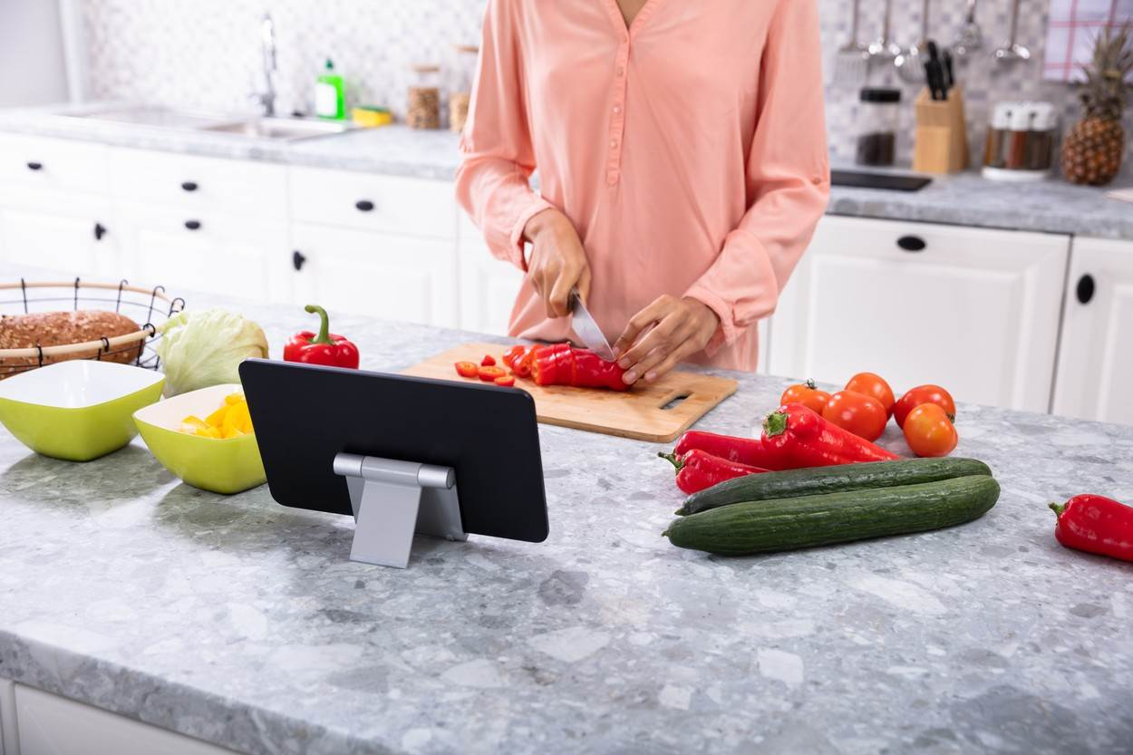 tablet;african;woman;vegetables;chopping;using;american;cooking;computer;food;kitchen;digital;home;black;while;health;bell;room;electric;house;board;life;cucumber;cutting;people;piece;person;tech;red;chili;standing;technology;young;electronic;internet;tomato;casual;wood;female;knife;vegetable;wooden;domestic;bowl;surfing;lifestyle;wireless;adult;one;sharp