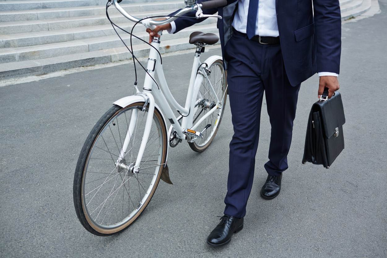 business;businesspeople;businessman;person;man;adult;young;employee;job;one;contemporary;agent;going;bicycle;briefcase;urban;closeup;human;walking;moving;leg;carrying;asphalt;wheel;formalwear